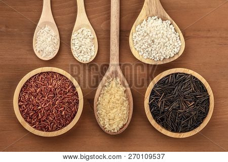 A Collection Of Various Rice Types, Shot From The Top On A Dark Rustic Wooden Background With Copy S