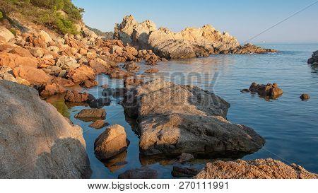Sea Beach In Spain. Stones In Water Coast. Sea Landscape Of Spanish Beach. Beautiful View Of Rocky C