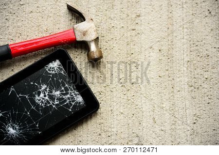 Broken Tablet With Hammer Near It