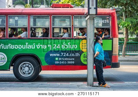 Bangkok, Thailand - November 2018: Woman Standing On The Street Leaning Against A Pole, A Red Bus Wi