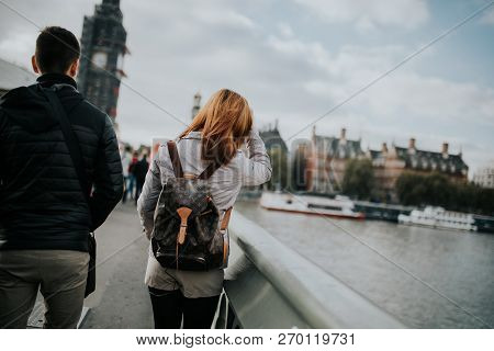 London, England - 25th October, 2018: Young Couple In Their Backs, Walking By Westminster Bridge, Wi