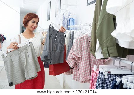 Smiling Young Indian Woman Choosing Between Two Pairs Of Shorts In Shop