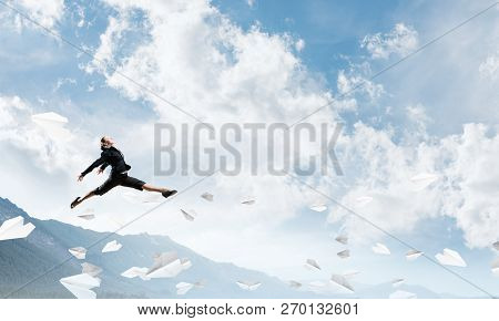 Attractive Business Woman In Suit Jumping In The Air Among Flying Paper Planes As Symbol Of Active L