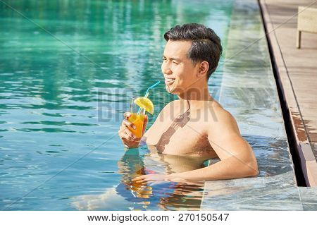 Smilng Attractive Asian Young Man Drinking Fresh Cocktail And Enjoying Sunny Day In Pool