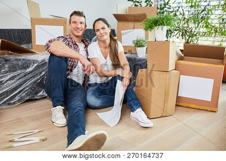 Young couple between moving boxes when moving to new apartment or house