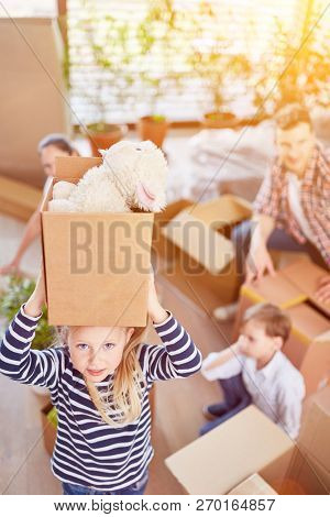 Girl carries moving box with cuddly toys when moving to a family home