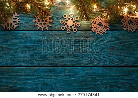 Image of blue wooden surface with burning New Year garland, snowflakes, spruce branches.