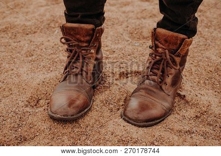 Image Of Unrecognizable Man Stands On Sandy Ground In Brown Leather Old Shaggy Shoes With Laces. Men