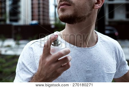 Man With Perfume. Happy Man Point Finger At Perfume Bottle