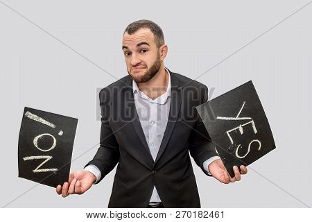 Ypung Businessman In Suit Hold Two Black Tablets With Written Words Yes And No. He Looks On Camera.
