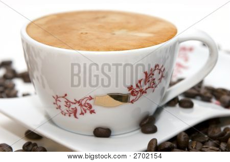 Cup Of Coffee And Grains Over White
