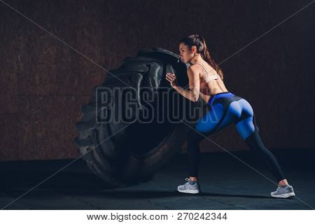 Fitness Woman Flipping Wheel Tire In Gym. Fit Female Athlete Working Out With A Huge Tire. Back View