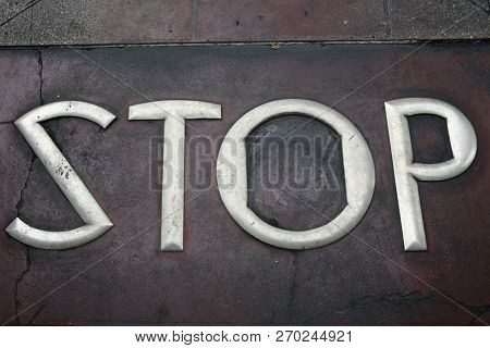 Metal Words in the Sidewalk. Old Metal Words imbedded in cement. The word STOP written in STEEL Letters Cemented into the sidewalk.