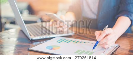 Business Woman Working On Analysis Charts And Graphs Showing Results.her Hand Holds The Pen And Poin