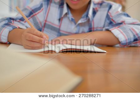 Young Little Asian Kid Boy Schoolboy Writing Drawing On Notebook. Child Children Doing Homework. Chi
