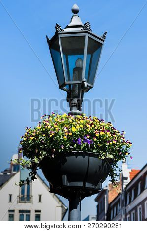 Old-fashioned Lamppost Decorated With Flowers In The Old Town Of Riga, Latvia