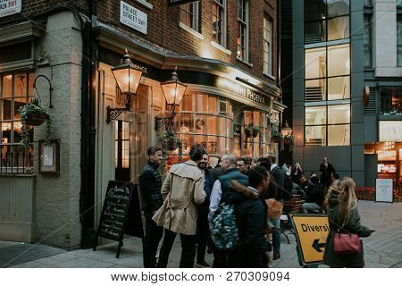 London, England - 25th October, 2018: A Group Of Friends Having A Drink Together At An English Pub T