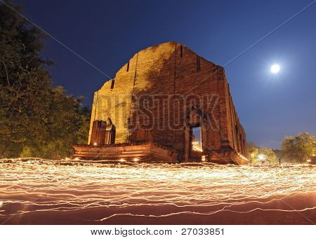 candle light trail of Buddhism Ceremony at temple ruin with moon on Asalha Puja Day