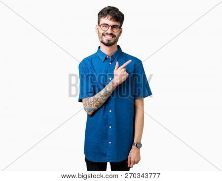 Young handsome man wearing glasses over isolated background cheerful with a smile of face pointing with hand and finger up to the side with happy and natural expression on face