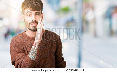 Young handsome man wearing winter sweater over isolated background hand on mouth telling secret rumor, whispering malicious talk conversation