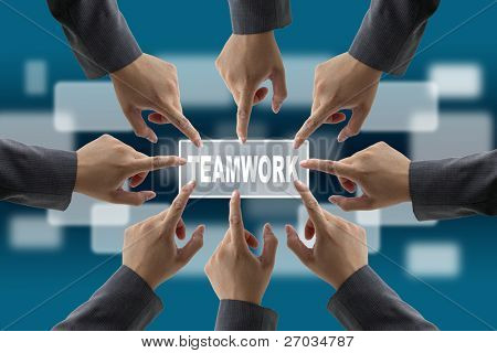 A diverse business team with hands together push teamwork button