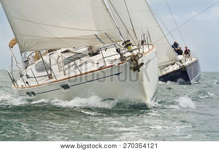 Two beautiful white yachts, sailboats or sail boats sailing or racing at sea