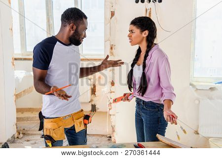 Side View Of Irritated Woman Talking To Boyfriend Doing Shrug Gesture During Renovation At Home