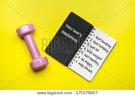 New Year Healthy Goals And Resolutions Concept. New Year's Resolutions Written On Black Notebook Pap