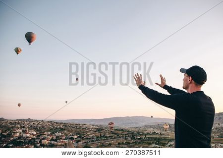 A man in solitude admires a beautiful view of the flying balloons in Cappadocia in Turkey. poster
