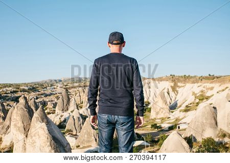 A man stands on top of a mountain in solitude, admires the beautiful view of the natural landscape in Cappadocia in Turkey poster