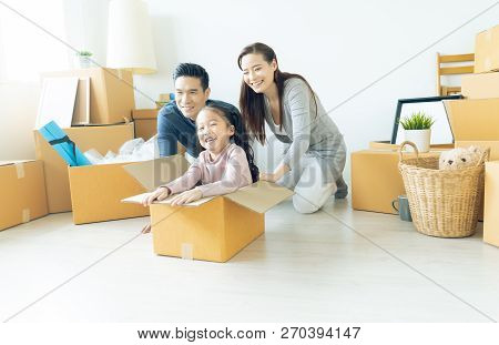 Happy Young Asian Family Of Three Having Fun Moving With Cardboard Boxes In New House At Moving Day.