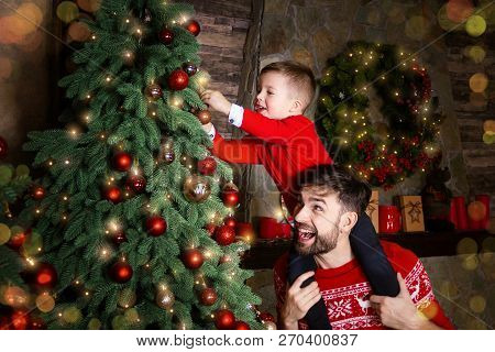 Happy Father And Son Enjoying Decorating Christmas Tree With Christmas Balls And Light Garland Prepa