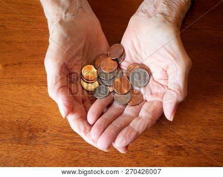 Elderly Woman's Hands Holding Multiple Coins