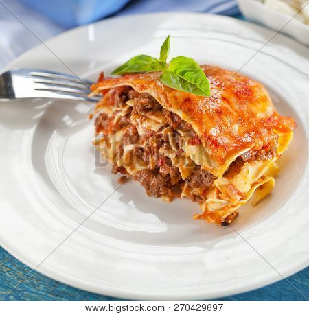 Tasty Lasagne With Meat Covered With Cheese Served On White Plate