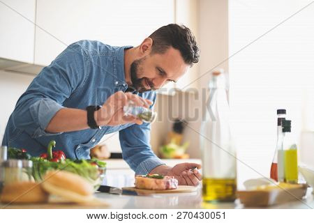 Young Man Adding Spices To Meat While Standing Near Kitchen Table