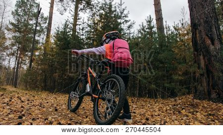 One Caucasian Children Walk With Bike In Autumn Park. Little Girl Walking Black Orange Cycle In Fore