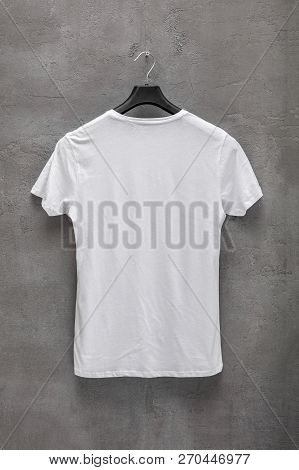 Back Side Of Male White Cotton T-shirt On A Hanger And A Concrete Wall In The Background