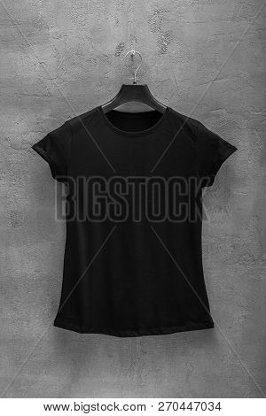 Front Side Of Female Black Cotton T-shirt On A Hanger And A Concrete Wall In The Background. T-shirt