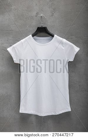 Front Side Of Female White Cotton T-shirt On A Hanger And A Concrete Wall In The Background. T-shirt