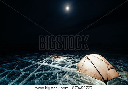 Fire On Ice At Night. Campground On Ice. Tent Stands Next To Bonfire. Lake Baikal. Nearby There Is C