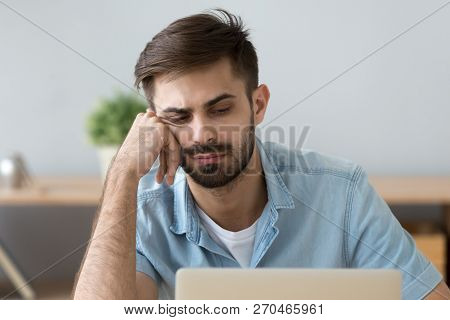 Lazy man feel unmotivated sitting near laptop at home poster