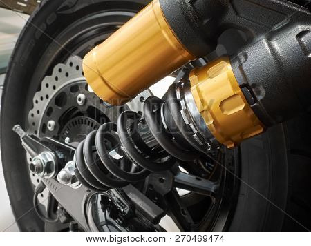 Side view on motorcycle rear chassis suspension with damper, coil spring,  wheel rim with tire, disc brake. Moto bike suspension close up poster