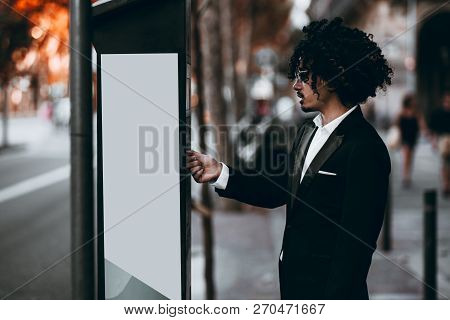 An Asian Businessman With Curly Hair And In Sunglasses Is Paying His Parking Time Via An Outdoor Ter