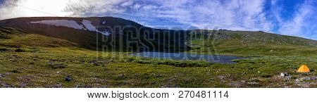 Beautiful Panorama Of Mountain Slopes With Snowfields And Clear Mountain Lake. Tent On The Backgroun