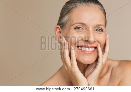 Beauty portrait of mature woman smiling with hand on face. Closeup face of happy senior woman feeling fresh after anti-aging treatment. Smiling beauty looking at camera with perfect skin.