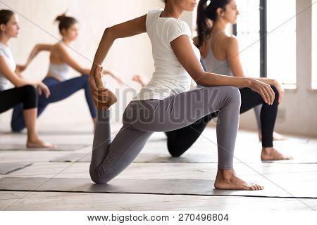 Group Of Young Women Practicing Yoga, Doing Anjaneyasana Exercis