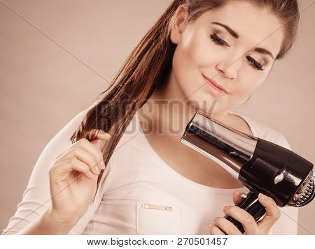Woman Drying Her Dark Brown Hair Using Hair Dryer. Studio Shot On Grey Background.