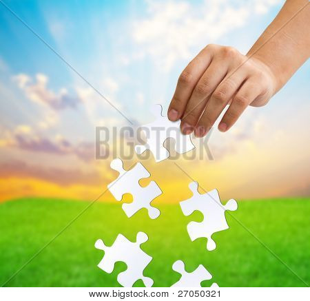 A hand catching falling puzzle pieces. Problem solving concept.