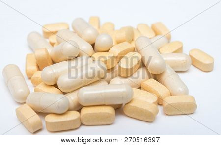 Medicine Yellow Pills Or Capsules On A White Background Close-up. Vitamins Drug Prescription Of Drug