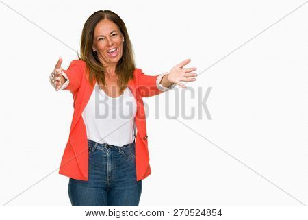 Beautiful middle age business adult woman over isolated background looking at the camera smiling with open arms for hug. Cheerful expression embracing happiness.